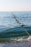 Buoy rope barrier on the water with floats Stock Images