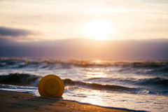 A buoy by the sea in back-light with a cloudy sky and a setting sun Stock Images