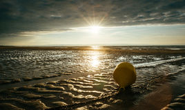 A buoy by the sea in low tide in back-light with a cloudy sky and a setting sun. Taken in Cabourg, Normandy, France royalty free stock images