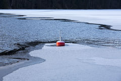 Buoy in the water. Some parts of the water is already frozen. Buoy in the freezing water surrounded by ice Stock Photos