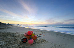 Buoys Ahoy. A wheelbarrow full of boat buoys on at Durley Chine beach with Bournemouth pier in the background Royalty Free Stock Photography