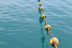 Buoys and deep blue sea. Yellow buoys and rope floating on the sea surface stock photo