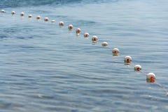 Buoys on fish net floating on surface of water. On stony beach, Kamenjak peninsula by the Adriatic Sea, Premantura, Croatia, sunny summer day royalty free stock images