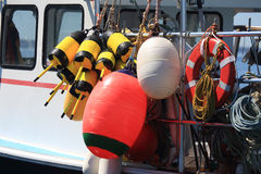 Buoys and Floats. In Bass Harbor ME, a collection of colorful floats, buoys, ropes and a life saver line one side of a docked lobster boat Stock Photo