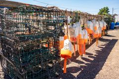 Buoys hang on a rack next to lobster traps stock images
