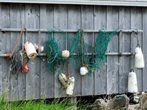 Buoys hanging on fish shack. Buoys and fish net hanging on a fish shack in Broadcove Lunenburg County Nova Scotia Canada Royalty Free Stock Image