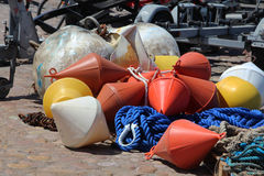 Buoys. Orange, yellow and white buoys lie on the heap, blue, white rope, rusty chains, photo close-up Royalty Free Stock Images