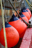 Buoys Protecting a Docked Ship in Alaska. Orange Buoys protecting a docked ship in an Alaskan harbor Royalty Free Stock Images