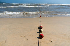 Buoys on a rope leading into the ocean Royalty Free Stock Photography