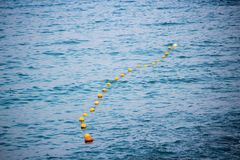 Buoys strung together and floating on water Royalty Free Stock Images