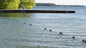 Buoys strung together by rope along beautiful blue lake to create safe swimming area for swimmers. Dock with ladders in background Royalty Free Stock Images