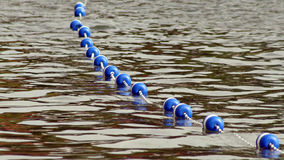 Buoys strung together by rope along lake to create safe swimming area for swimmers Stock Photography