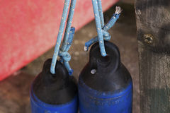 Buoys. Two dark blue buoys hanging in turquoise rope with a coral colored boat in the background Royalty Free Stock Photo
