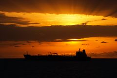 Buque de carga bajo puesta del sol Foto de archivo libre de regalías