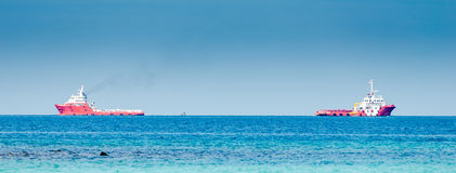 Buque de carga de dos rojos en el mar azul profundo Imagen de archivo