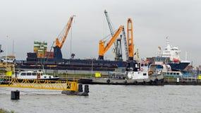 Buque de carga del carguero de graneles con las grúas de la cubierta bajo cargamento en puerto Foto de archivo