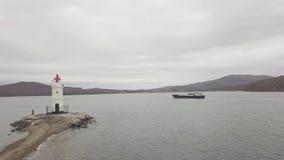 Buque de carga que flota en el mar y el faro en la opinión de orilla de mar del abejón del vuelo metrajes