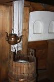 Buque de cobre para el agua potable (caldera con dos canalones) dentro de una casa de madera tradicional en el norte ruso Imágenes de archivo libres de regalías