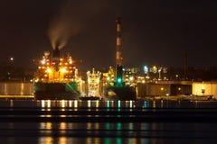 Buque de petróleo que descarga el cargo en la noche imagenes de archivo