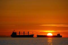 Buques de carga en la puesta del sol Fotos de archivo libres de regalías