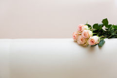 Buquet of tea roses on a white sofa. Bouquet of tea roses on a white sofa Royalty Free Stock Photography