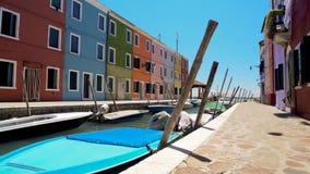 Burano有汽艇的海岛运河沿有五颜六色的大厦的街道停泊了 图库摄影