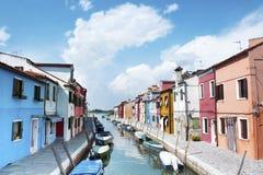 Burano海岛,意大利-一条街道的美丽的景色有五颜六色的房子和运河的 威尼斯明信片 免版税图库摄影