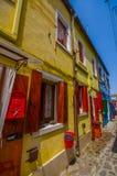 BURANO,意大利- 2015年6月14日:有美丽的颜色房子的老石街道在边, pinturesque邻里 库存图片