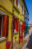 BURANO,意大利- 2015年6月14日:有美丽的颜色房子的老石街道在边, pinturesque邻里 库存照片