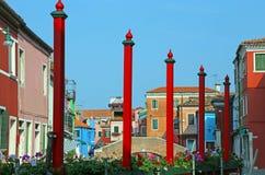 Burano ö i Italien färgrika hus och röda poler Arkivbild