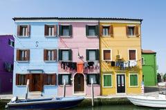 Burano ö, Venedig, Italien - färgrika hus med hängande kläder arkivfoton