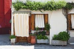 Burano ö, Venedig, Italien - fasaden av ett hus med härliga gardiner near fönstret och dörren Royaltyfria Bilder