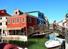 BURANO, ΙΤΑΛΊΑ - 9 ΑΥΓΟΎΣΤΟΥ 2016: τουρίστες στη γέφυρα και ζωηρόχρωμα σπίτια σε Burano, Βενετία, Ιταλία Στοκ Φωτογραφία