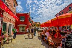 BURANO, ИТАЛИЯ - 14-ОЕ ИЮНЯ 2015: Люди наслаждаясь снаружи, летний день в Италии, ресторанах с зонтиками солнца снаружи Стоковые Фото