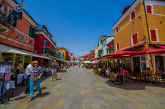 BURANO, ИТАЛИЯ - 14-ОЕ ИЮНЯ 2015: Улица Colorfull с домами на стороне различных цветов, turists наслаждаясь летом Стоковая Фотография