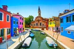 威尼斯地标, Burano海岛运河、五颜六色的房子、教会和小船,意大利 图库摄影