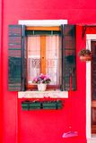 Burano. Colorful window on a  red facade in the old town of Burano, a little island  in Venice lagoon, Italy Stock Photo