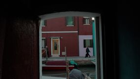 Burano houses and canal viewed through the doorway, Italy stock footage