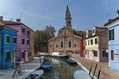 Burano island canal, colorful houses church and boats, Italy. royalty free stock image