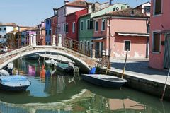 Burano island, Venice, Italy - view of canal, colorful houses, boats and a bridge Royalty Free Stock Photography