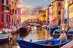 Burano island in Venice Italy picturesque sunset over canal with boats among old colourful houses stone streets. Royalty Free Stock Images
