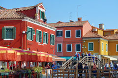 Burano island, Venice, Italy. BURANO, ITALY - SEPT 26, 2014: Central street between colorful houses on the famous island Burano, Venice. Venice and the Venetian Stock Image