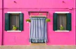 BURANO, ITÁLIA - 2 de setembro de 2016 Cor cor-de-rosa das paredes, duas janelas, flores na soleira Vista típica de Burano islan Imagem de Stock Royalty Free