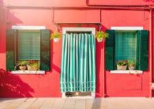 BURANO, ITALIË - 2 September, 2016 Een oranje huis met twee vensters en een deur Verfraaid met bloemen Typische mening van royalty-vrije stock afbeelding