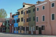 BURANO, ITALIA - 18 APRILE 2009: Via con le costruzioni variopinte nell'isola di Burano, una piccola città gentile in pieno dei c fotografia stock