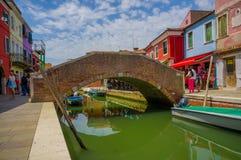 BURANO, ITALIA - 14 GIUGNO 2015: Ponte piacevole adorabile in mezzo ai canali in Burano, case dell'acqua di colore dai lati Fotografie Stock Libere da Diritti