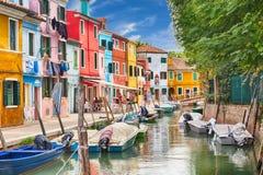BURANO, ITALIA - SETTEMBRE 2017: Case variopinte con le barche nell'isola di Burano con cielo blu nuvoloso vicino a Venezia, Ital Fotografie Stock
