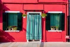 BURANO, ITALIA - 2 settembre 2016 Una casa arancio con due finestre e una porta Decorato con i fiori Vista tipica di fotografia stock libera da diritti