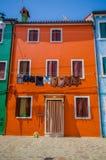 BURANO, ITALIE - 14 JUIN 2015 : Peu de maison dans la couleur orange, les diverses fenêtres et des vêtements humides dehors Photo stock