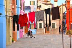 Burano, Italie La vue des maisons colorées et la cour avec les tissus de blanchisserie à sécher dehors et la femme agée détendent photographie stock